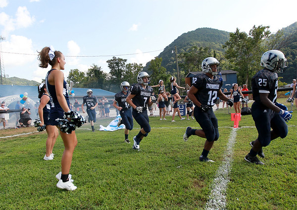 Valley High's football team rushes onto the field for their seasoned opener against Clay-Battelle at their new field in Smithers on Friday. (Chris Jackson/The Register-Herald)