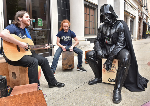 (Brad Davis/The Register-Herald) In a scene one normally wouldn't expect to see at such an event, Darth Vader chills out and keeps a beat as he jams with brothers David, left, and Levi Salts at the Coda Nights booth during the Kids Classic Festival Saturday.