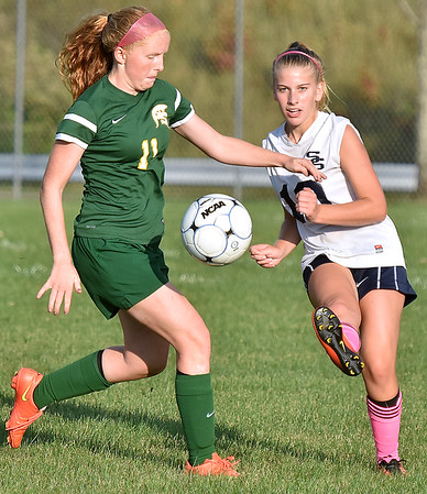 (Brad Davis/The Register-Herald) Shady Spring's #10 sends the ball downfield as Greenbrier East's Kate Perkins converges on her during the Tigers' game against the Spartans Thursday night at the YMCA Paul Cline Memorial Sports Complex.