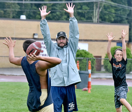 (Brad Davis/The Register-Herald) Shady Spring head coach Vince Culicerto and his son Cal, right, simulate leaping defenders as quarterback Joe Cantley, left, throws at his target, the trash can in the background, during Tigers football practice Wednesday afternoon.