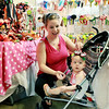 "Ashley Stiltner, from Davey, tries on a bow on her 8-month-old daughter's head at Beverly Watson's ""Chloe Lia"" booth<br /> Friday during the opening day of the annual Appalachian Arts and Craft Fair at the Beckley Raleigh County Convention Center. (Chris Jackson/The Register-Herald)"