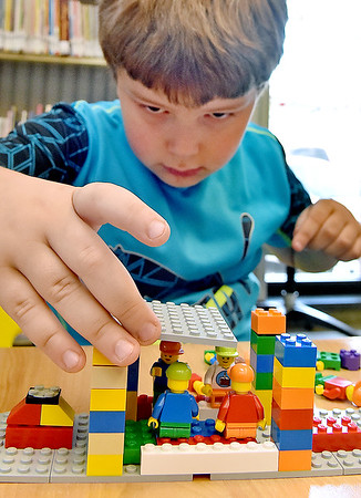 (Brad Davis/The Register-Herald) Six-year-old Pineyview resident Kolten Cummings concentrates as he constructs a space ship out of Legos during a building contest at the Raleigh County Public Library Thursday evening.