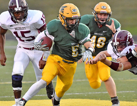 (Brad Davis/The Register-Herald) Greenbrier East's William Honaker eludes Woodrow Wilson's Jordan Hancock, left, and Ellis Lilly, right as he rumbles forward with the ball Friday night in Fairlea