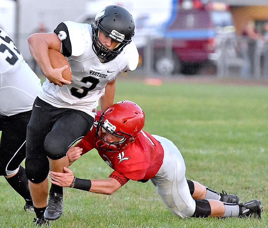 (Brad Davis/The Register-Herald) Westside's Josh Morgan breaks a would-be tackle from Liberty's Cruize Carico during the Renegades' season-opening win over the Raiders Friday night in Glen Daniel.