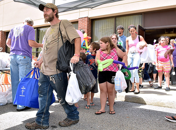 (Brad Davis/The Register-Herald) Area residents get all the groceries they can carry as volunteers distribute them in an orderly manner during the 4th annual Day of Hope Saturday afternoon at the Beckley-Raleigh County Convention Center.