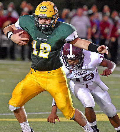 (Brad Davis/The Register-Herald) Greenbrier East quarterback Devin Persinger eludes Woodrow Wilson's Deontray Smith Friday night in Fairlea.