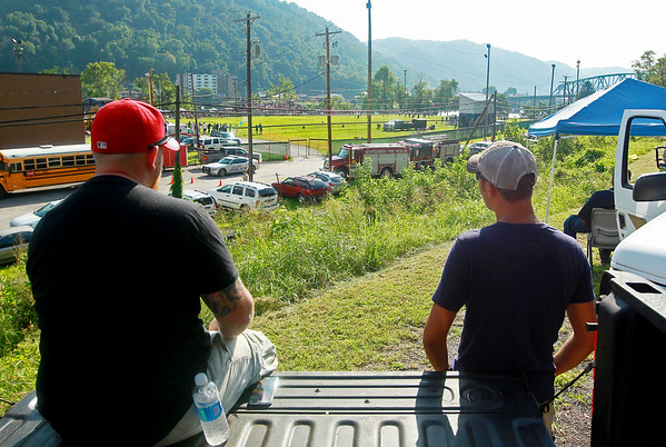 CJ Sizemore, left, and Sean Myers, both from Smithers, watch the Valley High's football team's season opener from the tailgate of Sizemore's truck in Smithers on Friday. This was the first ever game played at the new football field at the high school. (Chris Jackson/The Register-Herald)