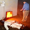 (Brad Davis/The Register-Herald) Mike Jude, training instructor at the National Mine Health and Safety Academy, demonstrates how a digital fire extinguishing training system is used during a tour of the underground mine simulation facility Wednesday afternoon. It's harder than it looks, as the trainee must must be able to completely extinguish the flames with only a limited amount of extinguisher.