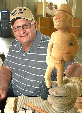 Lance Brooks, of Fairdale, owner of Midnight Carver, holds a wooden carving he made of Tom Brady holding a deflated football at the West Virginia State Fair in Fairlea.<br /> (Rick Barbero/The Register-Herald)