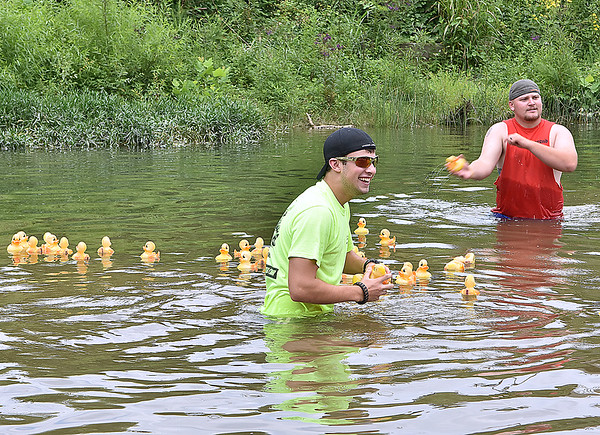 (Brad Davis/The Register-Herald) Official ducky wranglers David Staley, left, and Jacob Woodrum try to keep the flock on course during this year's Great Rubber Ducky Race in Hinton Sunday afternoon next to Veterans Memorial Bridge in Hinton.