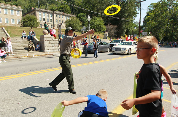 Katy Smith with the Army Corp of Engineers tosses a frisbee to parade goers during the annual Pineville Labor Day Parade on Monday. (Chris Jackson/The Register-Herald)