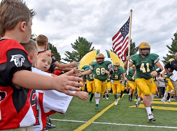 (Brad Davis/The Register-Herald) Young football players from the area youth league rach out to high five the Spartans as they take the field for their game against Woodrow Wilson Friday night in Fairlea.