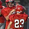 (Brad Davis/The Register-Herald) Liberty's Zach Williams, left, helps teammate Dalton Pettry fix a malfuntioning helmet strap Friday night in Glen Daniel.