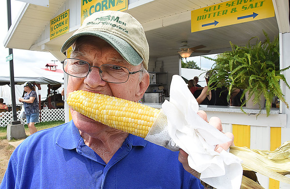 Mike Akers, of Charleston, eating a roasted corn at the West Virginia State Fair in Fairlea.<br /> (Rick Barbero/The Register-Herald)