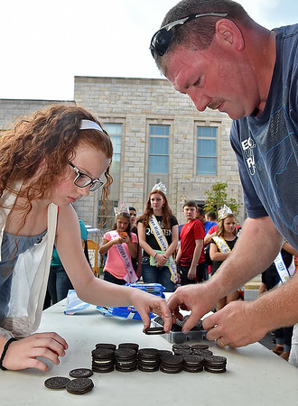 (Brad Davis/The Register-Herald) The focused and experienced cookie stacking duo of 11-year-old Makaila Bolen and her dad Jason get to business as they compete in the Oreo Stacking Contest during Taste of Beckley Saturday. The two competed in the event last year as well.