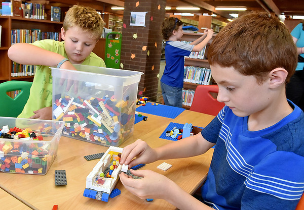 (Brad Davis/The Register-Herald) Nine-year-old Joseph Murphy, right, constructs what he called a solar powered bus out of Legos during a building contest at the Raleigh County Public Library Thursday evening. Nine-year-old Haden Hiser, left, and eight-year-old Wesley Bostic, background, also participate.