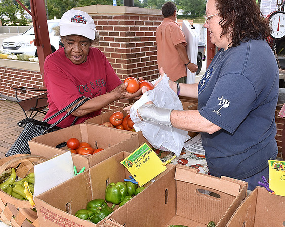 (Brad Davis/The Register-Herald) Beckley resident Mozella Kidd gets some fresh tomatoes while the gettin' is good from Pluto Road farmer Shirley Meadows, right, who ended up selling most of her fresh vegetables at the Uptown Tailgate Farmer's Market Friday afternoon atop Beckley's Intermodal Gateway.