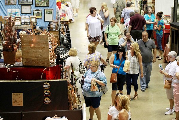 Fair goers browse booths Friday during the opening day of the annual Appalachian Arts and Craft Fair at the Beckley Raleigh County Convention Center. (Chris Jackson/The Register-Herald)