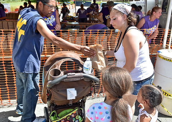 (Brad Davis/The Register-Herald) Tyrone Anderson and Cassie Goodman get lunch for her kids Malia, 7, Peytan, 3, and 5-month old Tyrone at the 4th annual Day of Hope Saturday.