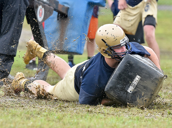 (Brad Davis/The Register-Herald) Shady Spring's Stephen Crook splashes down in the mud as he and his Tigers teammates work on tackling drills during a rainy practice Wednesday afternoon.