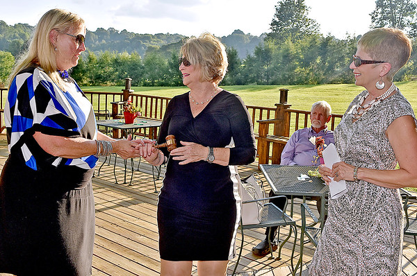 (Brad Davis/The Register-Herald) New Beckley Board of Realtors President Kay Booth, middle, receives a ceremonial gavel from outgoing president Cathy Smith, left, as Paula Miller of the West Virginia Association of Realtors, right, officiates the installation ceremony for new officers Thursday evening at Daniel Vineyards in Crab Orchard. Other officers installed were Paige Powers (1st VP), Mike Tyree (2nd VP), Diane Meador-Cole (Secretary), Jerry Zaferatos (Treasurer), Marla Sinko (Director '19), Pam Lynch (Director '18), Beth Keatley (Director '18) and Tim Berry (Director '17).
