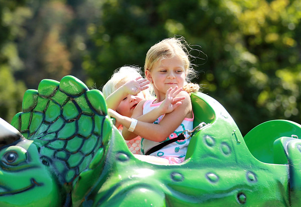 Kymber, 6, and Khyler, 2, Davis wave to their parents on a ride during the carnival as part of the annual Pineville Labor Day Parade on Monday. (Chris Jackson/The Register-Herald)