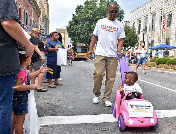 (Brad Davis/The Register-Herald) Little Addison Rogers is pushed around by her grandfather Spanky Francis during the Kids Classic Festival parade Saturday.
