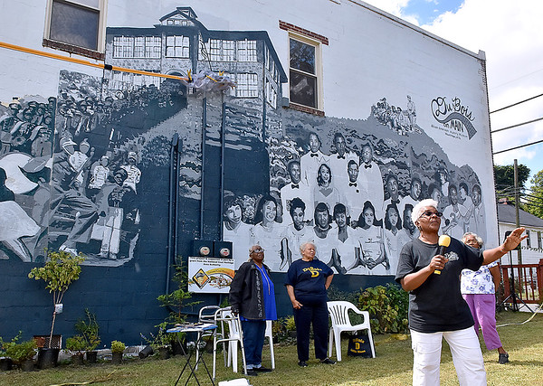 (Brad Davis/The Register-Herald) Jean Evansmore (bottom right), president of DuBois on Main, says a few words of thanks to all involved following a ribbon cutting ceremony and open house for a new mural on the side of the Mt. Hope museum Saturday afternoon. Looking on in the background are alumni (from left) Alma Freeman-Fleming, Louis Christian-White and Bernice Clayton (hidden behind Evansmore).