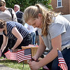 (Brad Davis/The Register-Herald) Sister Clare, right, and Mikeal Bates place American flags around the September 11th Memorial prior to a special ceremony at Word Park Sunday afternoon.