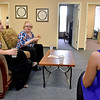 (Brad Davis/The Register-Herald) Attendees (from left) Matina Clapsis, Sharon Minor and Amanda Buchanan lounge inside the new office building for the Family Refuge Center prior to a ribbon cutting ceremony Thursday afternoon in Lewisburg.
