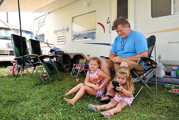 Darren Thomas, of Williamsburg, hanging out with his two grandchildren, Calleigh Rudd, 5, and Riyah Cook, 2, in front of his camper at the West Virginia State Fair in Fairlea.<br /> (Rick Barbero/The Register-Herald)