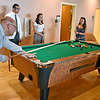 (Brad Davis/The Register-Herald) At left, Dr. Brian Griffith, a biochemical instructor at the school, breaks while joining in a game of pool with students (from left) Devin Francillon, Rebecca Rickard and Melissa Villa inside the new Student Center on the campus of the West Virginia School of Osteopathic Medicine Friday afternoon in Lewisburg.