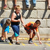 Three boys run to collect candy thrown during the annual Pineville Labor Day Parade on Monday. (Chris Jackson/The Register-Herald)