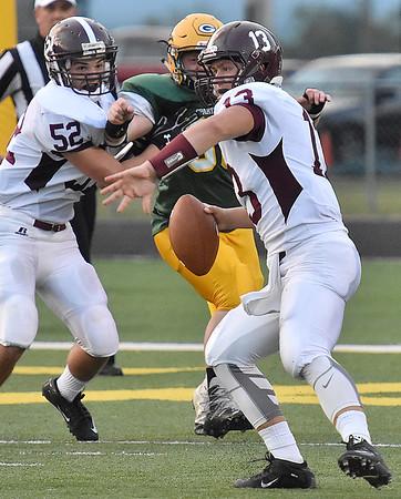 (Brad Davis/The Register-Herald) Woodrow Wilson quarterback Sutton Radford looks for an open receiver under pressure Friday night in Fairlea.