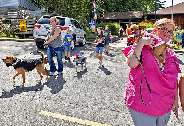 (Brad Davis/The Register-Herald) Participants and their dressed up pooches make their way to the gazebo area so the judges can get a look at them during the Kid's Clasic Pet Pageant Sunday afternoon at the Youth Museum.