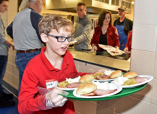 (Brad Davis/The Register-Herald) Young volunteer Brody Young, 10, turns to carry a tray full of hot meals to a waiting table of guests during United Methodist Temple's Community Christmas Dinner Sunday afternoon inside The Place.