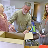 (Brad Davis/The Register-Herald) David Neal (middle), Disaster Program Manager for the American Red Cross's WV Region-Southest Chapter, reaches in and draws a ticket from a box of hundreds of entries for special angel-themed quilt to support flood victims in areas that didn't receive as much aid money as others Thursday afternoon at their Industrial Drive headquarters. Red Cross Chief Development Officer Cynthia Hemphill-Reehling, right, and Glen Fork resident Hazel Hurley, who lead the effort to raise the money, look on. Donna Lester was drawn as the winner of the quilt.