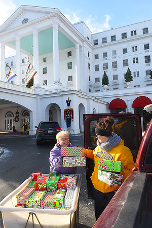 Linda Simms, left and Mary Beth Altizer, both with Case West Virginia, load up Christmas gifts during the Dream Tree Children distribution held at The Greenbrier Resort. The gifts are for the Right from the Start program.<br /> (Rick Barbero/The Register-Herald)