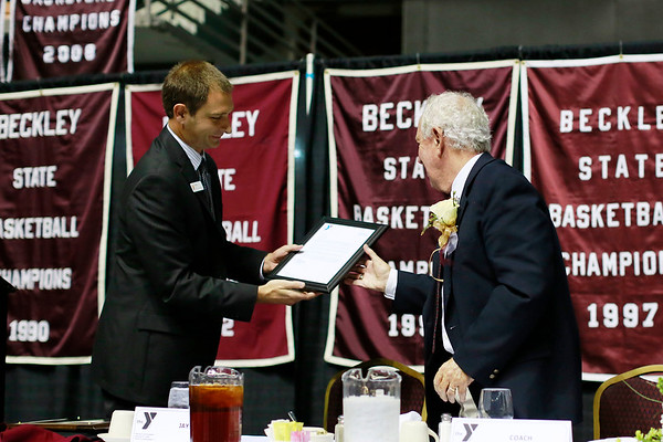 YMCA of Southern West Virginia CEO Jay Rist hands Dave Barksdale a letter from the YMCA during the Spirit of Beckley Awards Monday at the Beckley-Raleigh County Convention Center. (Chris Jackson/The Register-Herald)