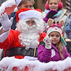 (Brad Davis/The Register-Herald) A busy Santa Claus waves to spectators as he rolls up Neville Street during Beckley's Christmas Parade Saturday afternoon.
