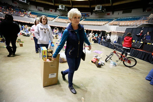 Volunteers help carry items outduring the Mac's Toy Fund at the Beckley-Raleigh County Convention Center on Saturday. (Chris Jackson/The Register-Herald)