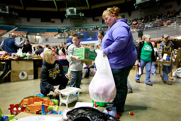Andrea Brush, left, from Ghent, and Noah Brush, 8, help Lorelei Smith, from Mabscott, with toys during the Mac's Toy Fund at the Beckley-Raleigh County Convention Center on Saturday. (Chris Jackson/The Register-Herald)