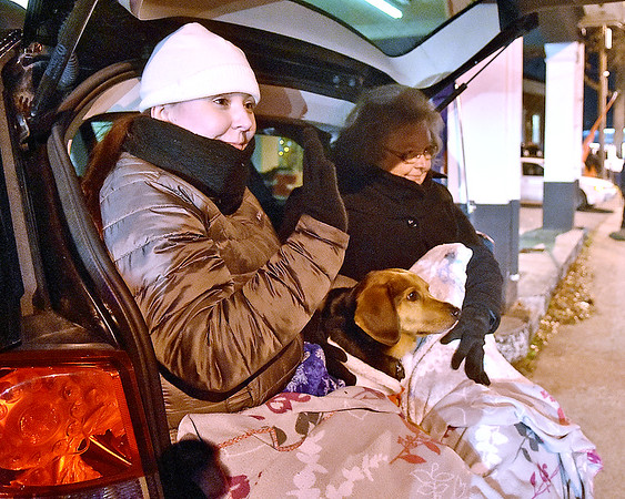 (Brad Davis/The Register-Herald) Oak Hill residents Rachel Johnson, near, her mother Judy and their five-year-old beagle/hound mix Ernie stay warm as they wave at parade participants from the tailgate of their SUV during Oak Hill's Christmas Parade Thursday night.
