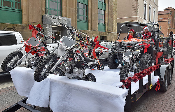 (Brad Davis/The Register-Herald) Mini dirtbikes are the reindeer and a 4x4 is the sled on the ATV Parts Plus team's creative float during the Beckley Christmas Parade Saturday afternoon.