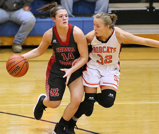 (Brad Davis/The Register-Herald) Cabell Midland's Sierra Womack holds off Summer's County's Whittney Justice as she moves the ball up the court during the Rogers Oil Classic championship game Saturday night in Hinton.