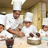 Devin Couvan, asst. executive pastry chef, second from left, helps Piere Suteau, left,  Jean Marc Suteau and Mary Suteau, make strawberry penguins during Apprentice Day held at The Greenbrier Resort.<br /> (Rick Barbero/The Register-Herald)