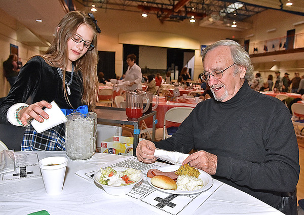 (Brad Davis/The Register-Herald) Young volunteer Emma Beebe, 11, gets some ice for Beckley resident Dave Leadingham's drink during United Methodist Temple's Community Christmas Dinner Sunday afternoon inside The Place.
