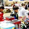 Children and adults look over toys during the Mac's Toy Fund at the Beckley-Raleigh County Convention Center on Saturday. (Chris Jackson/The Register-Herald)