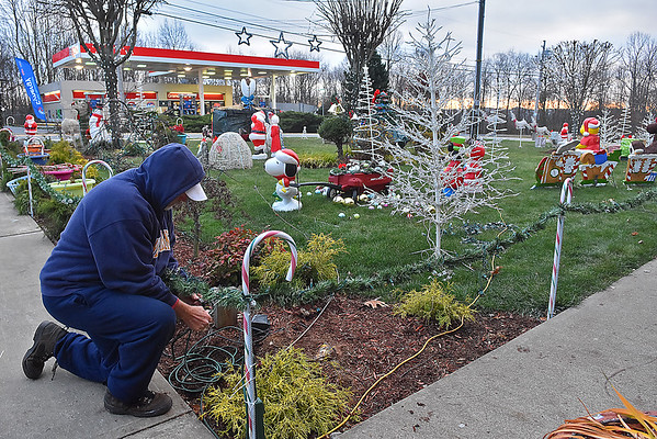 (Brad Davis/The Register-Herald) Area resident Walt Kiser kneels as he arranges a slew of wires to power the Christmas wonderland that his front yard has morphed into at his Grandview Road home Friday afternoon. Kiser, a retired coal miner formerly from Oceana, has a history of decking out his yard for Christmas and has accumulated tons of excess decorations that he's currently letting go in a garage sale. He's been working on this one since November 6th and says this will probably be one of the last big setups he'll do. Just travel Grandview Road towards Shady Spring and you can't miss his Christmas wonderland.