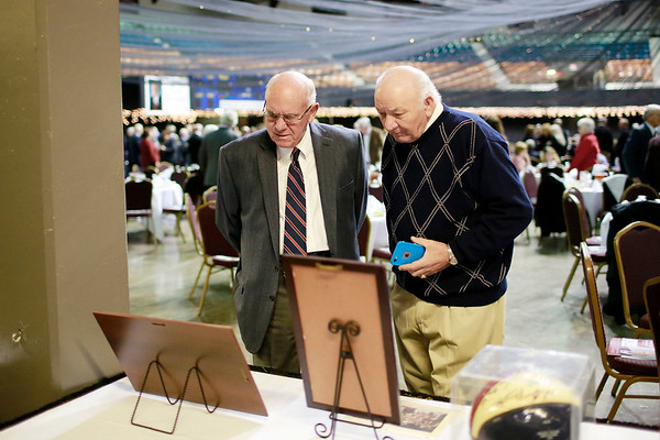 """Bob Gardner, left, and Robert """"Frog"""" Young look over old photos of coach Dave Barksdale during the Spirit of Beckley Awards Monday at the Beckley-Raleigh County Convention Center. (Chris Jackson/The Register-Herald)"""